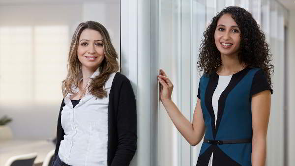 Two woman standing by an office glass wall.